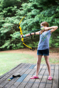 a young girl practicing archery