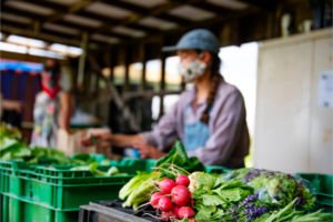A woman wearing a mask sells fresh produce at a farmers market