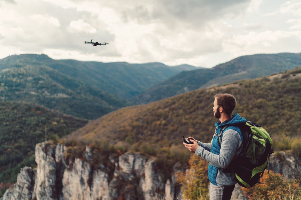 Man flies a drone over some wooded mountains