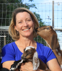 Kate Johnson posing with two goats.