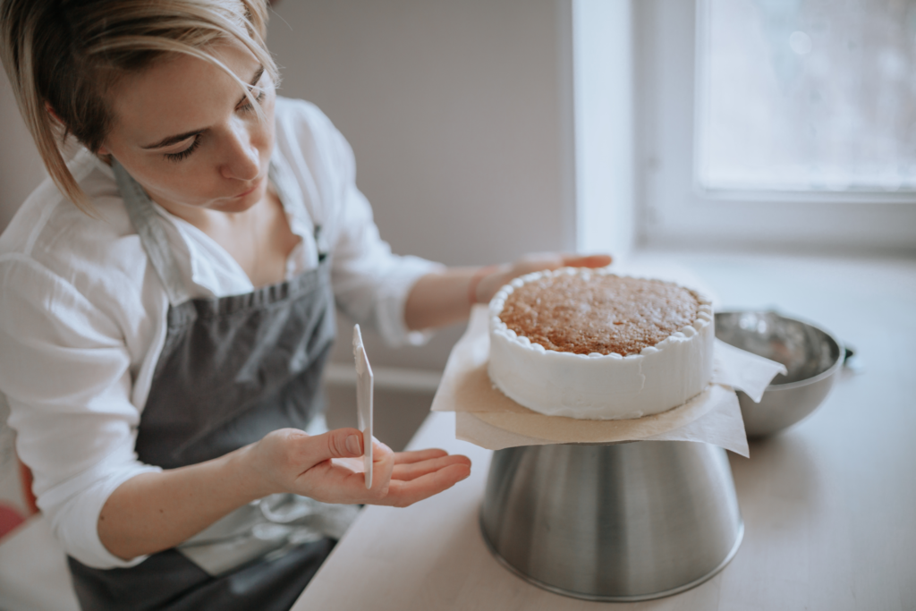 A woman decorates a cake at home.