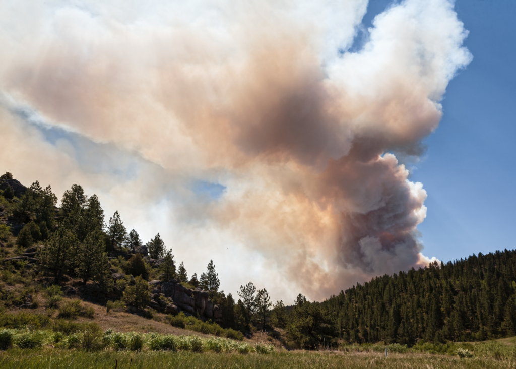 smoke from a wildfire billows over mountains in Colorado