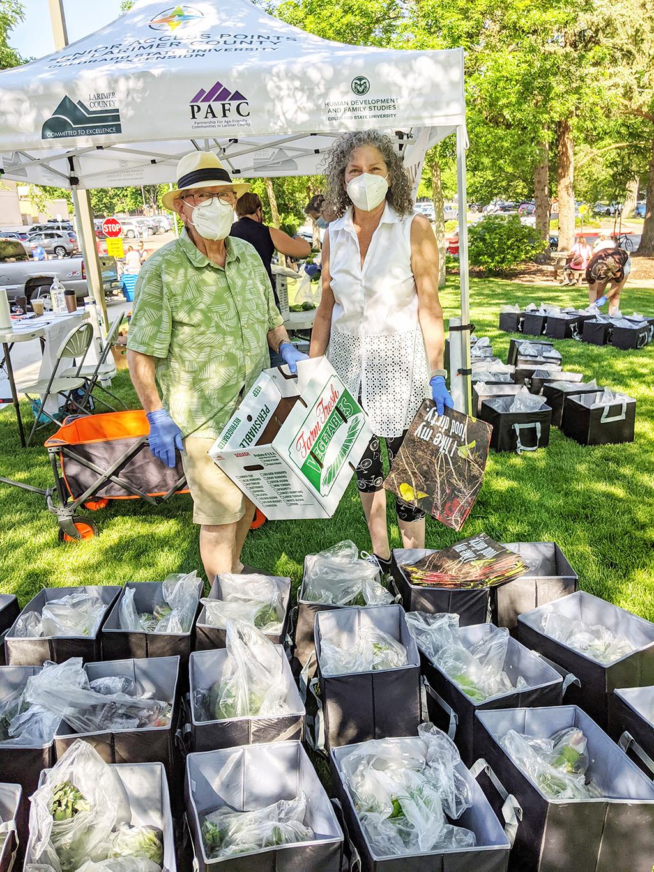two volunteers pack bags of produce